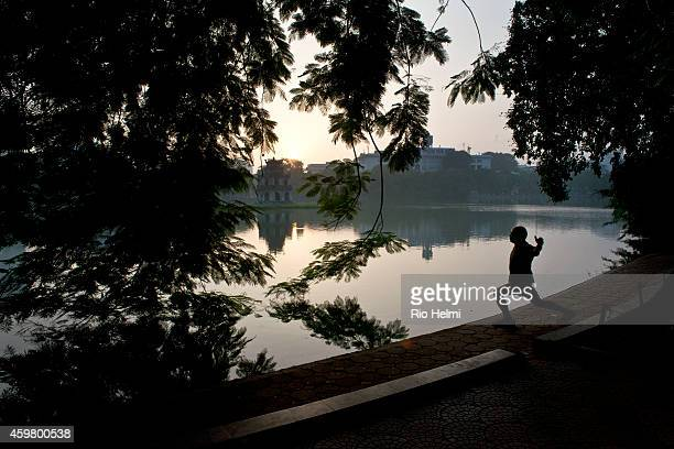 A man exercising vigorously at dawn on the Hoan Kiem Lake in the background in the lake is the Temple of the Returned Sword