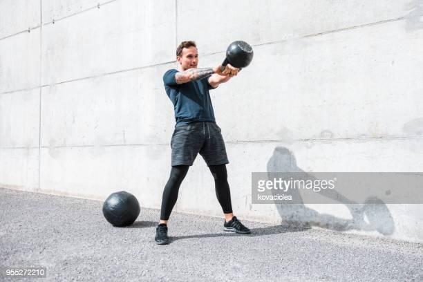 homem, exercitar-se com um kettlebell ao ar livre - kettlebell - fotografias e filmes do acervo