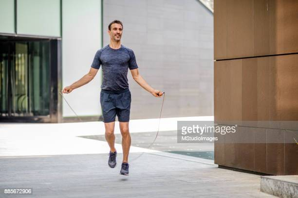 man exercising with jump-rope outdoors - skipping along stock photos and pictures