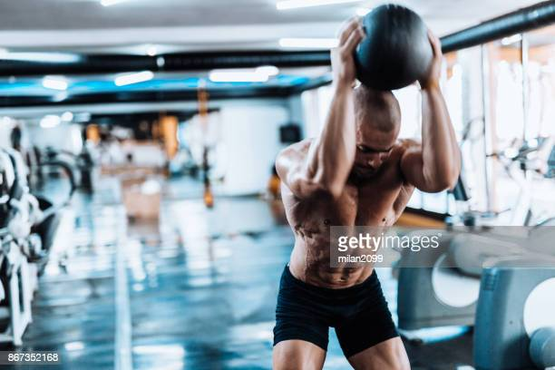 man exercising with medicine ball in the gym - medicine ball stock pictures, royalty-free photos & images