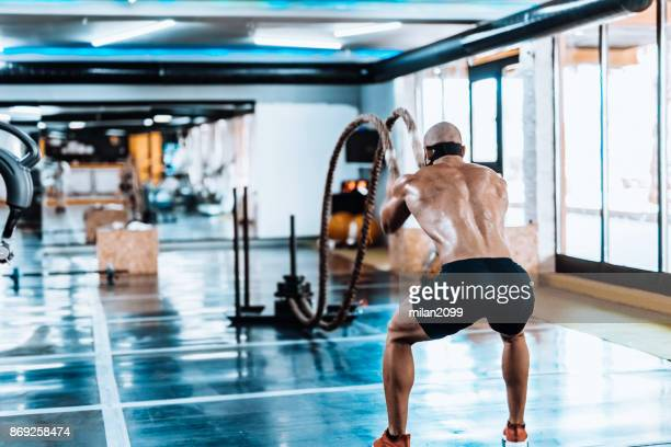 man exercising with rope in the gym - milan2099 stock photos and pictures