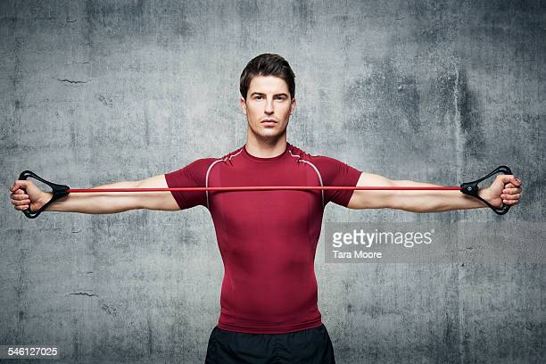 man exercising with stretch band in urban studio - maroon stock pictures, royalty-free photos & images