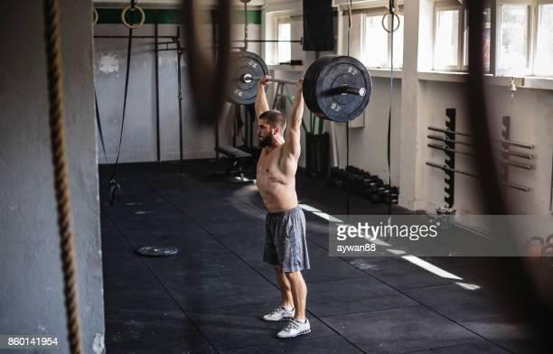 Homme faisant de l'exercice avec les poids et haltères