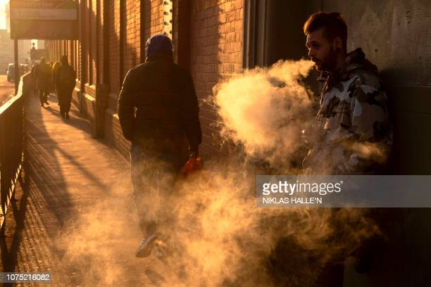 A man exhales a cloud off vapours as he smokes an electronic vaping machine outside Waterloo station in London on December 272018