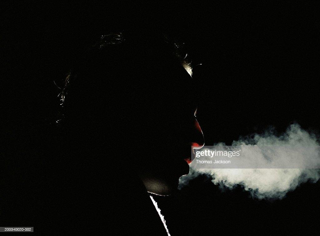 Man exhaling vapor, side view, close-up, night : Stock Photo
