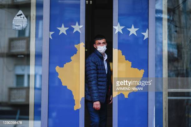 Man exits a government building decorated with Kosovo's flag in Pristina on December 22, 2020. - Kosovo was preparing to call a snap poll, after its...
