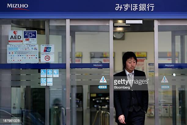 A man exits a Mizuho Bank Ltd branch in Tokyo Japan on Thursday Nov 14 2013 Mizuho Financial Group Inc Japan's thirdbiggest bank by market value...