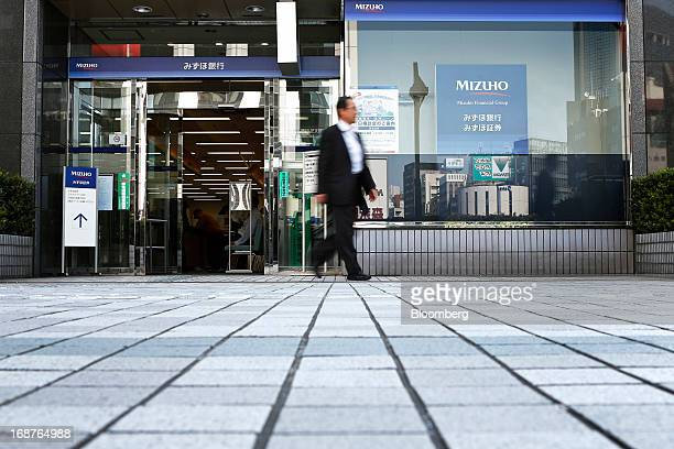 A man exits a Mizuho Bank Ltd branch in Tokyo Japan on Wednesday May 15 2013 Japan's three biggest banks led by Sumitomo Mitsui Financial Group Inc...
