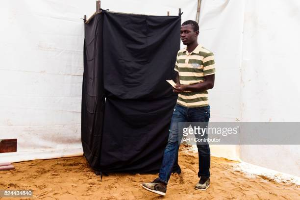 TOPSHOT A man exits a polling booth prior to casting her vote in Senegal's legislative election on July 30 2017 in Dakar Senegalese voters cast...
