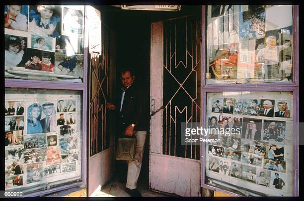 A man exits a shop whose windows are covered with photographs of King Hussein May 17 1998 in Amman Jordan Still a teenager when crowned in 1952 King...