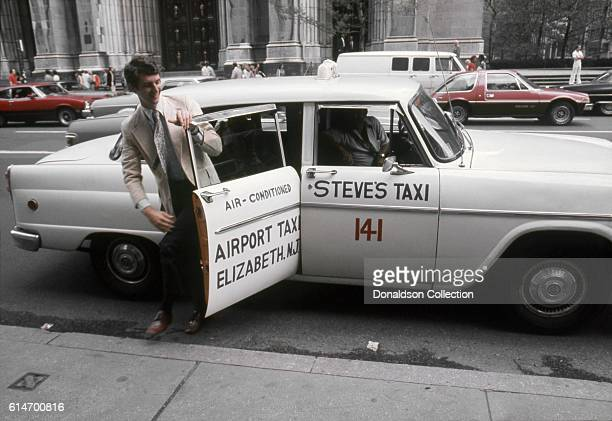 A man exits a Taxi and Airport Taxi based in Elizabeth New Jersey in1976 in New York City New York