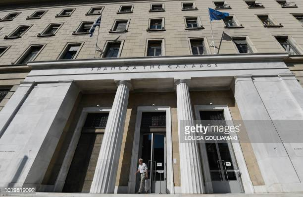 TOPSHOT A man exits the headquarters of the Bank of Greece in Athens on August 20 2018 After years of tough austerity measures Greece emerges on...