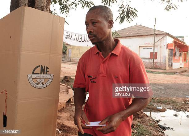 Man exits the voting booth to vote in the second round of the presidential election on May 18, 2014 in Bissau. Guinea-Bissau voted for a new...