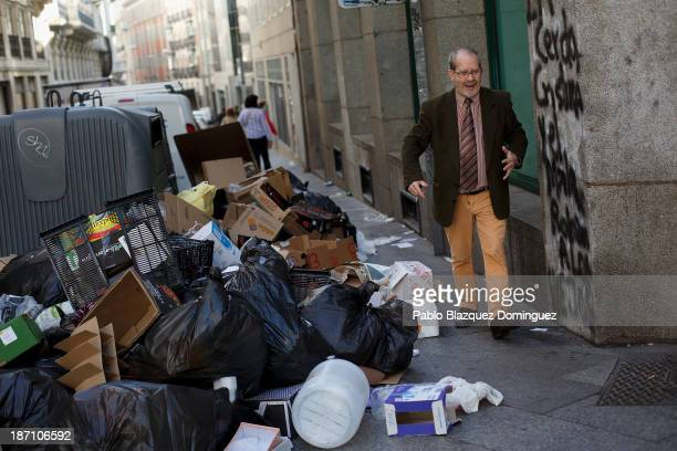A man exlaims as he walks by garbage dumped around rubbish bins in the street on November 6 2013 in Madrid Spain Street cleaners garbage collectors...