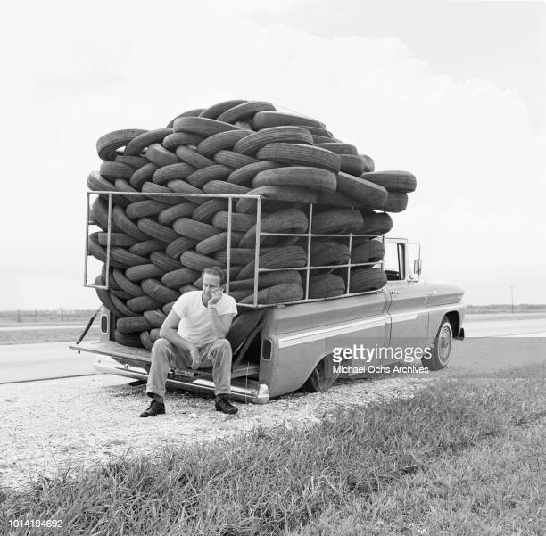 Man experiences irony as his car, laden with used tires, has a flat tire, Houston, Texas, March 1966.