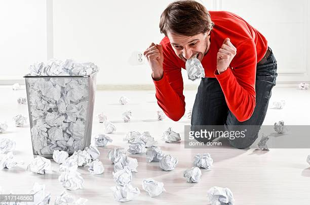 man experiencing creativity block, eating paper pages with anger - the_writer's_block stock pictures, royalty-free photos & images