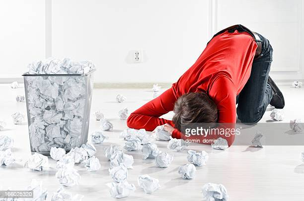 Man experiencing creativity block, many paper balls scattered on floor