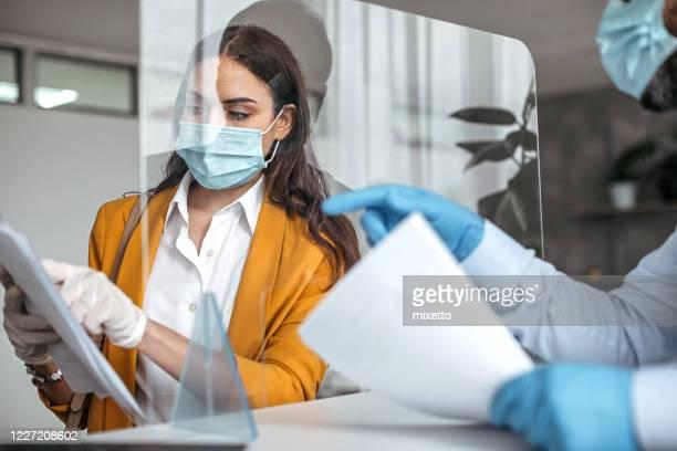 homme expliquant des documents au client féminin au compteur de banque - tenue de protection photos et images de collection