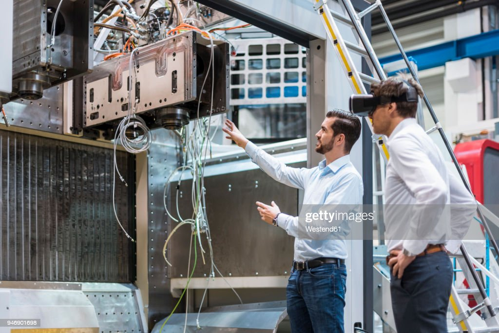 Man explaining machine to colleague wearing VR glasses in factory : Stock-Foto