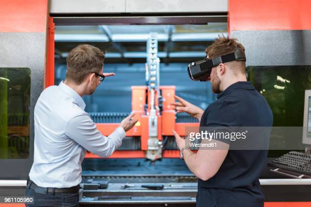 Man explaining machine to colleague wearing VR glasses in factory