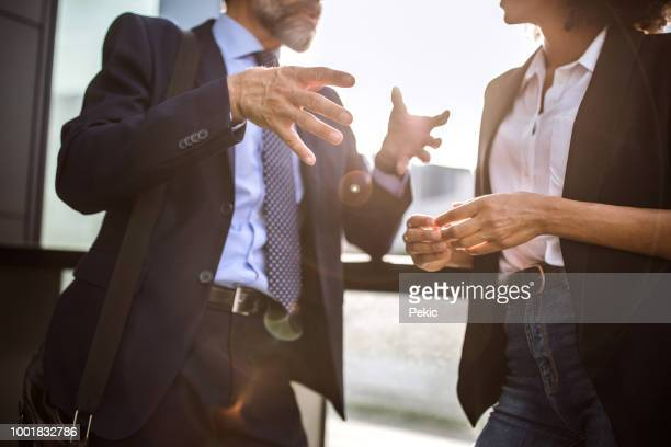 man explaining something, gesturing and having vivid chat with his female colleague - esprimere a gesti foto e immagini stock