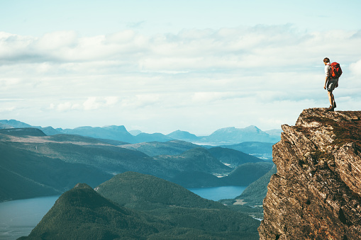 Man explorer standing on cliff alone mountain summit over fjord Norway landscape Travel Lifestyle success motivation concept adventure active vacations outdoor 1047121298