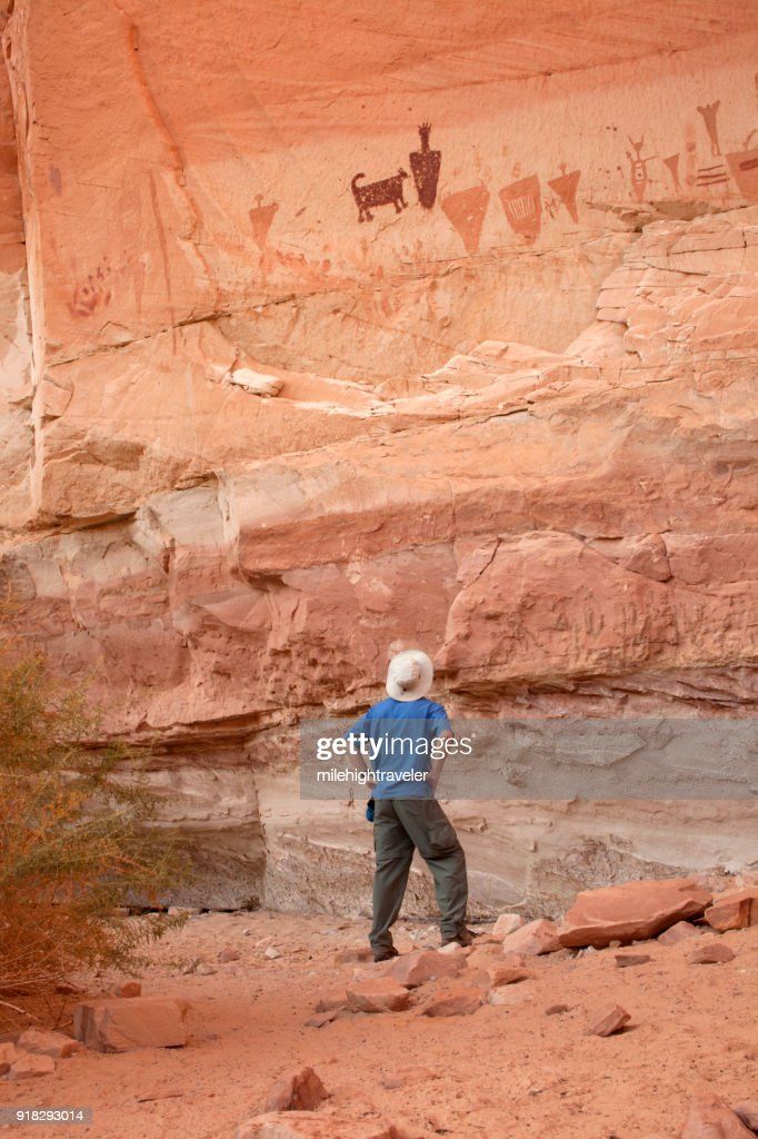 Man explores Horseshoe Canyon rock art pictographs Canyonlands National Park Utah : Stock Photo
