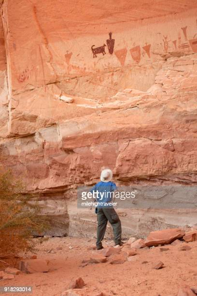 Man explores Horseshoe Canyon rock art pictographs Canyonlands National Park Utah