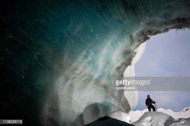 man exploring a stunning glacial ice cave - whistler british columbia stock pictures, royalty-free photos & images