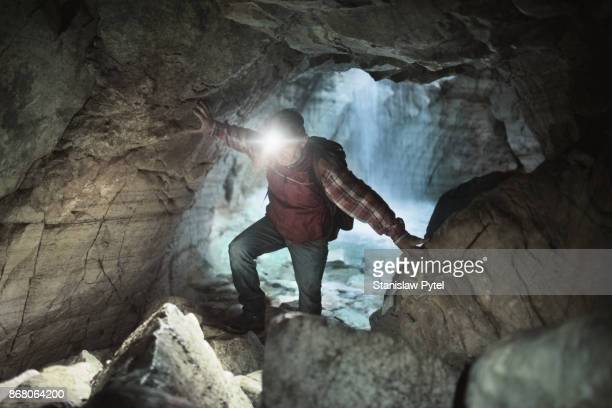 Man exploring cave with waterfall in background