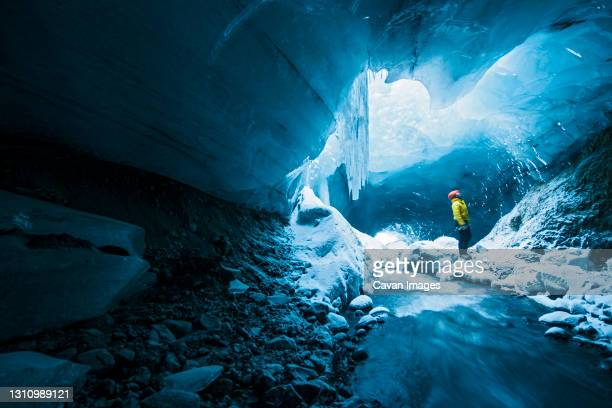 man exploring ice cave in thorsmork - iceland - iceland stock pictures, royalty-free photos & images