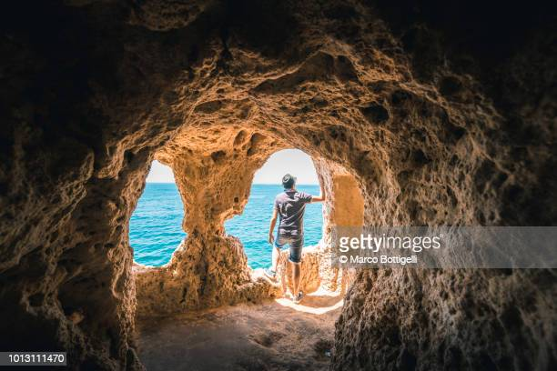 man exploring the algar seco rock formation, portugal - local landmark stock pictures, royalty-free photos & images