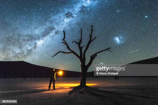 man exploring the desert with lantern at night - namib naukluft national park stock pictures, royalty-free photos & images