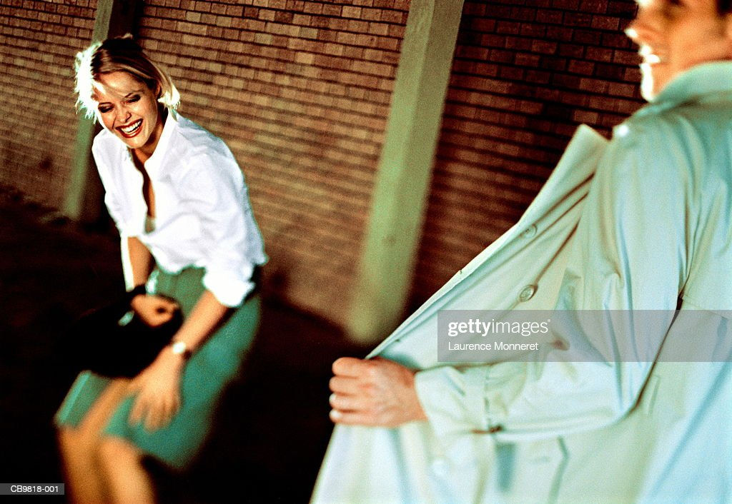 Man exposing himself in front of woman, woman in fits of laughter : Stock Photo