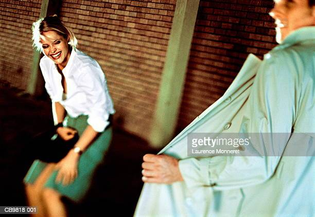 man exposing himself in front of woman, woman in fits of laughter - male flashers stock photos and pictures