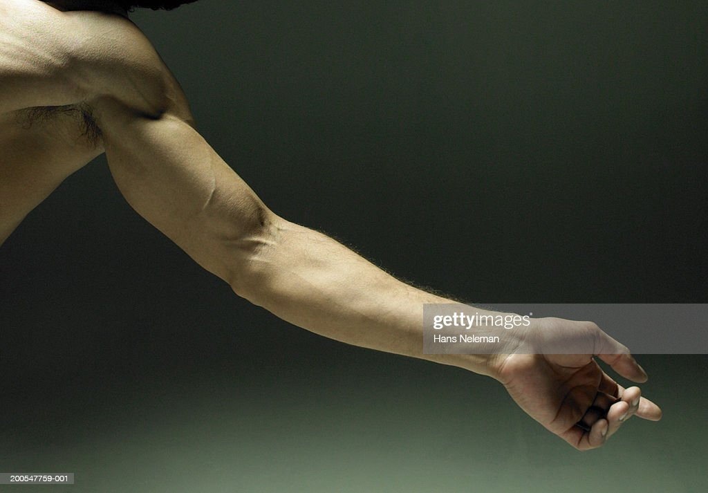 Man extending arm, close-up on arm : Stock-Foto