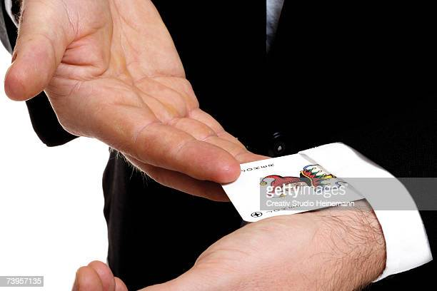 man extracting playing card out of sleeve, close-up, mid section - joker card stock photos and pictures