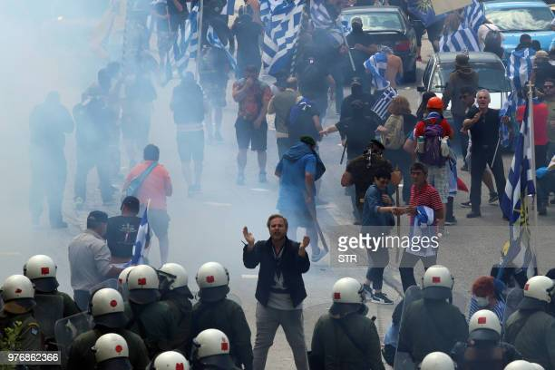 TOPSHOT A man face riot police as protestors holding Greek flags walk amid smoke during a protest at the village of Pisoderi near the border with...