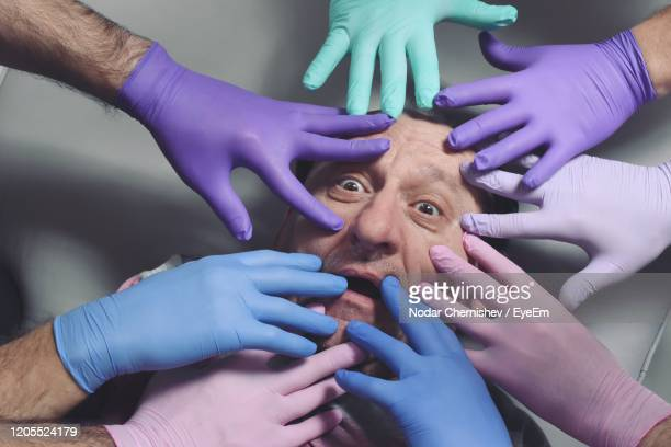 man face surrounded by human hands with gloves - omgeven stockfoto's en -beelden