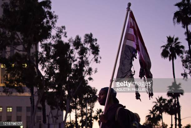 TOPSHOT A man faces a row of police holding a burnt upsidedown US flag as protesters gather in downtown Los Angeles on May 27 2020 to demonstrate...