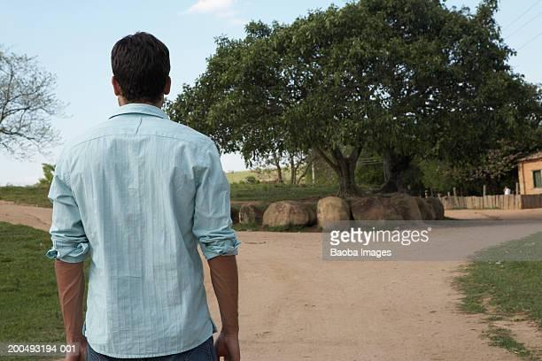 Man facing fork in dirt road, rear view