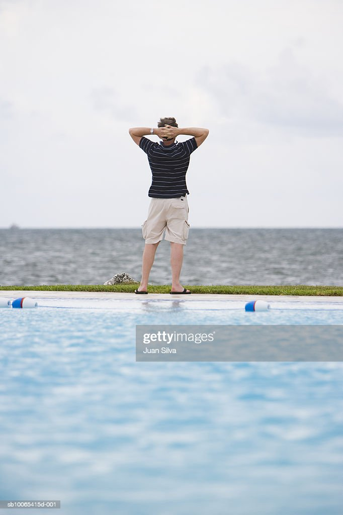 Man facing ocean with arms on neck, rear view : Foto stock
