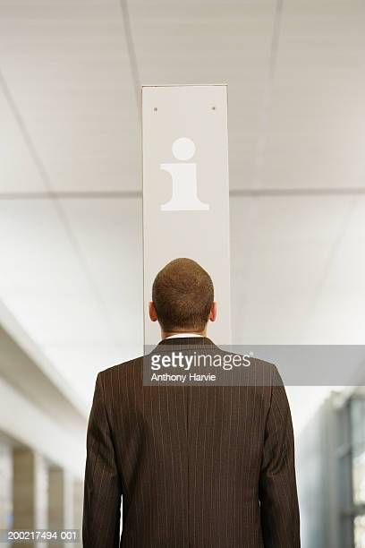 man facing sign for information point, rear view - striped suit stock pictures, royalty-free photos & images