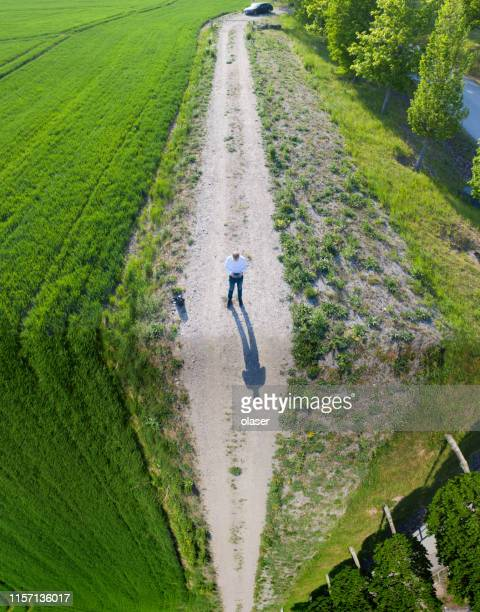 Man facing steep cliff illusion while flying drone