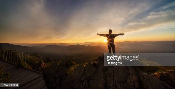 Man facing sunset with arm stretched