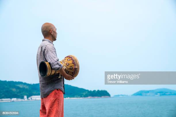 Man facing the ocean while holding and playing percussion instruments