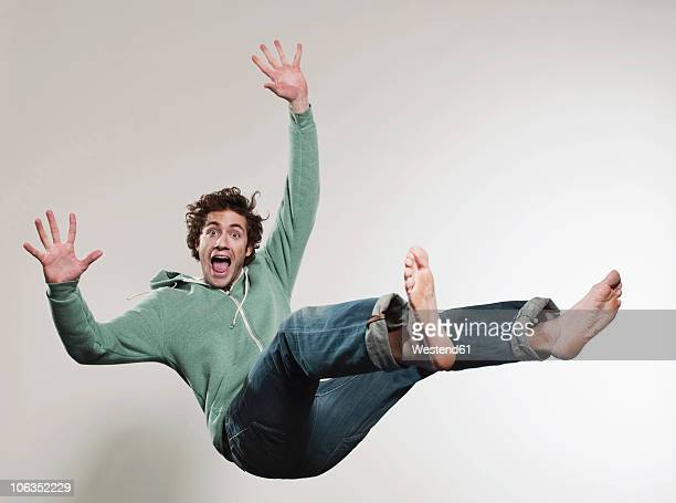 man falling against grey background, mouth open, portrait - in de lucht zwevend stockfoto's en -beelden