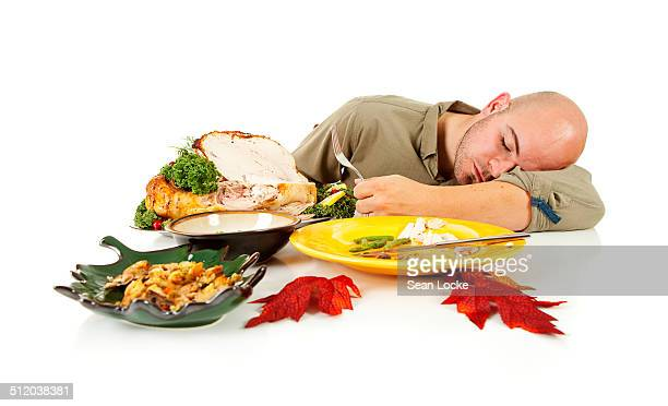 man falling asleep after dinner - thanksgiving leftovers stock photos and pictures