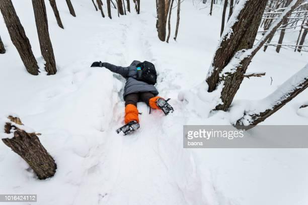 homme tombant sur la route de neige - lying down photos et images de collection
