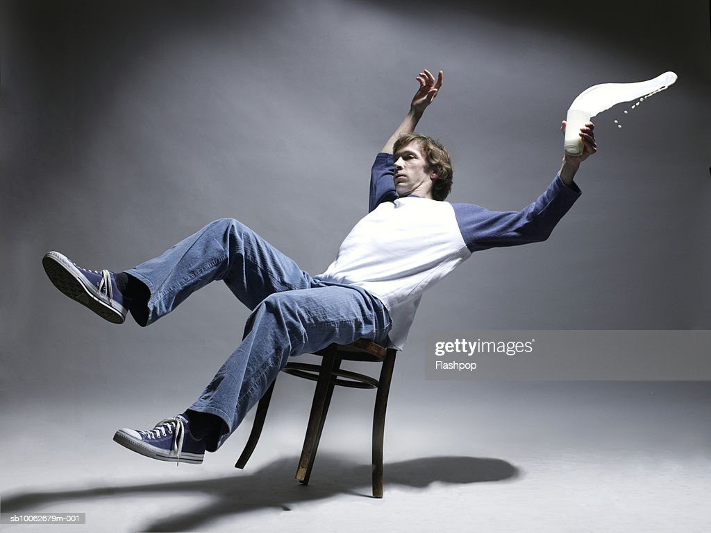 Man falling from chair holding glass of milk : Stock Photo